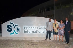 The new SXM brand logo and signage unveiled at the entrance area of Princess Juliana International Airport (SXM), on February 2, 2013, at 9:04 PM. L-R: Hon. Romeo Pantophlet, Minister of Transport, Economic Affairs and Telecommunications; Hon. Sarah Wescott-Williams, Prime Minister of St. Maarten; Ms. Regina LaBega, Managing Director of the SXM Airport operating company (PJIAE); Mr. Clarence Derby, Chairman of the Supervisory Board of Directors, PJIAE. (SXM Airport photo)