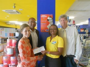 Kristen (left) accepts the $5,000 cheque from Harris' Sales & Retail Services Manager Kimberly Douglas. Also present are Adrian Brancker (second from left) and Archie Cuke (right) of the Team Kristen Charity