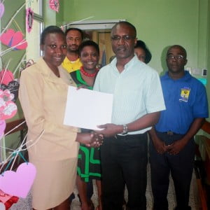 From left: Sharon Hartley receiving a gift certificate from CEO of BPI, David Jean-Marie for a weekend for two at the Crane Resort