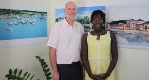 David Crichton, Interim Director of Trade and Investment Promotion at the Montserrat Development Corporation and Rochelle Lee, Manager of the One Stop Shop stand in front of some of the plans for the new town in Little Bay and the port in Carr's Bay.