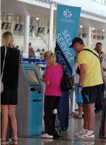 Passengers using the self-service kiosk at SXM. (SXM Airport photo)