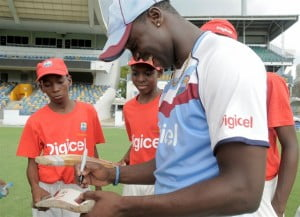 West Indies fast bowler, Kemar Roach, signs autographs for the eager young cricketers after a fun-filled session.