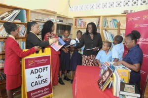 Staff from the Speightstown branch (from left): Cherilina Thomas, Sherry Ann Jackman, Sheri Rawlins and Cheryl Stoute, branch manager, assist students and teacher, Aquinda Harris (right) with restocking the shelves of the library at Roland Edwards Primary School.