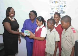 Principal of St. Mary's Primary School Ms. Jennifer Robinson (2nd from left) and excited students accepting the Study Steps software from Mrs. Jennifer Bradshaw-Wood, Divisional General Manager, Human Resources and Community Relations, GEL.