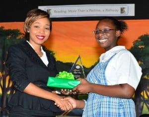 Arkayla Clarke receiving her Best Reader award from Gina Cummins, Group Marketing & Communications Coordinator with SOL (CARIBBEAN) LTD.