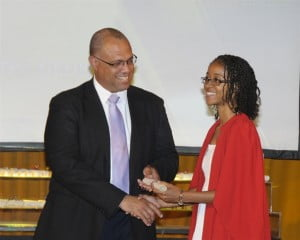 Anitra George receiving her scholarship award from Mark St. Hill, Managing Director Operating Company, CIBC FirstCaribbean International Bank.