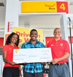Kirk King, Sales and Marketing manager of Sol Barbados Ltd joins Retail Sales Executive Denise Mendes, to present the Shell V-Power Drive in to Win Promotion Grand Prize of $10,000 in cash to a smiling Justin Greaves.