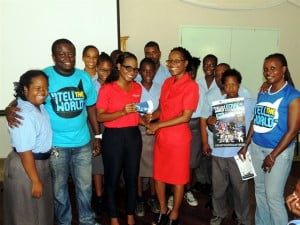 """Digicel Marketing Executive, Shakida Grant (left centre) presenting 30 tickets to the """"Tell the World – Lecrae"""" concert to Emelda Bell, Principal of the Ann Hill School. Also pictured are Paul Murrell (left), Promoter and Diana Wilson, Member of Kingdom Culture International, along with some of the students of the Ann Hill School."""