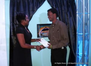 Marketing Manager of Barbados YP, Pam Roach hands Jabarrio Holligan his well deserved victory for a scintillating view of Bridgetown at Night, a back cover perhaps?