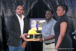 General Manager of Global Directories (C'bean) Colin Francis {jacketed} presents Corey reece with his Nikon D3200 camera with the blessings of B'dos Mktg. Mgr. Pam Roach