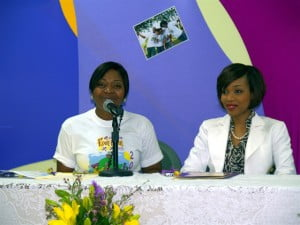 """Also speaking at the launch, organiser of the Fun Run, Dawn Lisa Callendar-Smith (in Tee Shirt at Head table with Ms Cummins) said this year's event promised to be even more fun, with special prizes on offer including an """"Auntie Olga look-alike prize"""". She also encouraged all schools to challenge perennial winners St. Winifred's and Convent for the prize being awarded to the largest school contingent."""