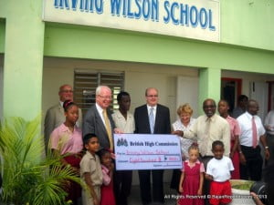 Lord Wallace of Tankerness presenting a cheque to Mr Wilmont Straughn, Principal of the Irving Wilson School with representatives from the British High Commission. From left, Phil Culligan, Deputy High Commissioner, Lord Wallace, Paul Brummell, High Commissioner, Gilly Metzgen, Political Officer, Wilmont Straughn with students from the school.