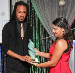 Larissa Jeanville of TRINRE presents Ayoung-Julien with Kaj's award for Most Promising Entrepreneur at the THA's BDU's 2012 Business Awards. Photo courtesy Kyle Keens-Dumas.