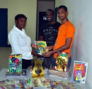 (from left to right) Loleta Parris Librarian with the National Library Service main branch accepts the donation of over 100 books from members of the Outsiders Underground Comicbook group Wade Alleyne and Rashid Holder.