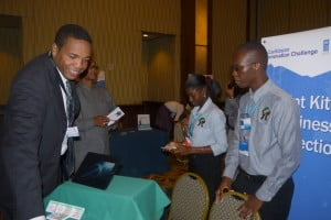 Minister of Youth Empowerment Honourable Glenn Phillip (left) visits the SKBC booth at the CIC Finals