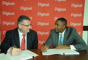 Digicel Group CEO, Colm Delves (left), and WICB President, Dave Cameron, share a joke as they complete the signing of the sponsorship contract.