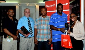 Andrew Straughn(left), activation coordinator for Mount Gay Rum, along with Shakida Grant (right), marketing executive with Digicel, presents Pedro Jordan (second right), James Norris (second left) and Romel Stuart with their prizes.