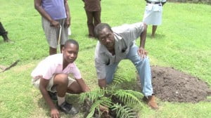 Mr Pogson with a Verchild's High student placing plant in the ground
