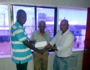 Journalist Rawle Nelson accepts the sponsorship cheque from Fleet Manager of Noble House Seafoods, Richard Jodan while Personnel Manger Mr. Corlette looks on with appreciation.