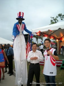Uncle Sam as a Moko-Jumbie shares a giggle with staff from the Chinese Embassy