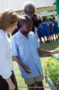Deputy Assistant Secretary of State Liliana Ayalde and Ambassador Larry L. Palmer get a closer view of what the students have planted in their garden.