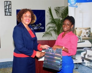 Margaret Hoyte, Marketing Manager at McEnearney Quality Inc., presents Chanice Hunte, Trimart Supermarkets with a prize during the recent orientation for new employees across ANSA McAL (Barbados) Ltd.