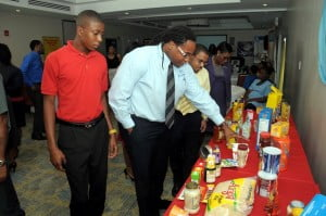 New employees within ANSA McAL (Barbados) Ltd. (from left) Akeel Evelyn, Trimart Supermarkets; and Komi Barrow, Stuart Bannister, and Melissa Grannum, all from Consolidated Finance, view a products' showcase.