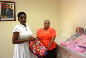 Left to Right:  Meshell Rawlins, Chairperson of the Coordinating Committee presenting bags to Denise Nurse, Deputy Director, Child Care Board.