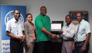Left to right – FAO representatives, Dr. Cedric Lazarus, FAO Livestock Development Officer, Mrs. Grace Brome, Administrative Associate/Procurement  and  Dr. Terence Mayers, Lead Technical Consultant for the project, present the donation to David  Elcock, Supervisor of the Veterinary Laboratory and Mr. Ralph Farnum, Chief Agricultural Officer (Ag).