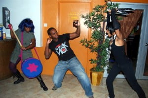 """Leandra Thompson and Tiffany Brewster dressed as characters from the film """"Scott Pilgrim"""" """"menace"""" Omar Kennedy (centre) co-founder of AnimeKon at the U.S. Embassy's """"Geekfest"""" film screening."""