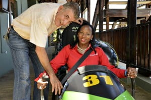 Director of Mystic Mountain, Mike Drakulich, gets ready to send off Digicel's Joy Clark, in the bobsled at the Mystic Mountain Rainforest in Ocho Rios, Jamaica.