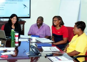 Angelique Beaubrun and Kevin Chase, facilitators from LCI Consulting Inc., the management consultancy which developed and delivered the programme, interact with participants: Peta Welch and Cheryl Haynes.