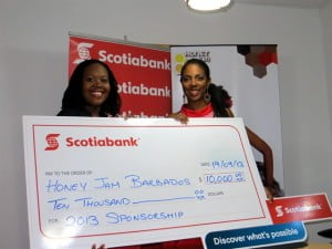 Scotiabank Marketing Manager Amanda Lynch-Foster (left) presents a sponsorship cheque to CEO of Honey Jam Barbados, Ebonnie Rowe (right)