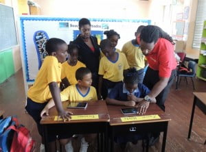 Digicel Marketing Executive, Marc Massiah (right) taking students of the Ellerton Special Unit through a tutorial on how to use their new Android tablets. Also pictured is Unit principal, Donna Holder.