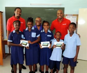 Students of the Erdiston Special School and principal, Cheryl Forde (centre), were very happy to receive the tablets donated to them by Digicel, represented here by Marketing Executives, Randy Howard (left) and Marc Massiah (left).