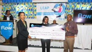 Gail Purcell, Country Manager of Flow Grenada (left) and Akirah Licorish (ctr) present a check for EC$ 1500 to Sturling Campbell of Boca Secondary School during the launch of Flows expanded Broadband service on Tuesday, October 1, 2013 at the Flamboyant Hotel, Grenada.