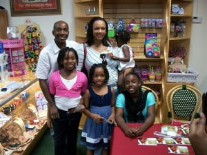 Barbadian, Ian Lavine, Detective Inspector with the Royal Cayman Islands Police Service, and his wife and daughters at an autograph signing with Makalah Harrison