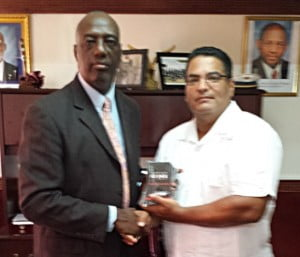 Commissioner Celvin G. Walwyn (left) accepts a free license from Mike Perez. Photo courtesy the Royal St. Christopher and Nevis Police Force