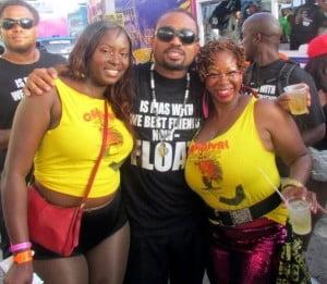 The Ladies of Carnival Concierge pose with Soca King Monarch Machel Montano