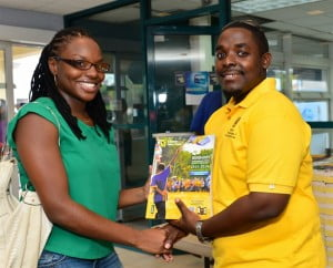 Ronnette Francis receiving her 2013/2014 Barbados Telephone Directory from Corey Reece who took the picture which is featured on the cover