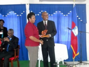 Claudia Jones receives a Medford Mahogany trophy for outstanding service from Hilford Murrell
