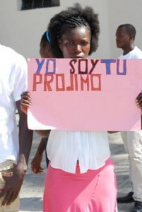 "Young woman holds up placard, with sentence that translates from Spanish as ""I am your neighbor,"" during a citizens rights demonstration in Santo Domingo, DR, 2013. (© Reconoci.do photo)"