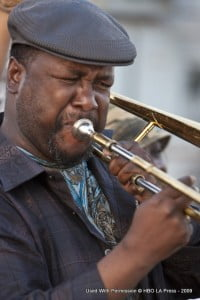 """Antoine Batiste (Wendell Pierce) joins the Rebirth Brass Band as the funk marches on in Scene 5 of the pilot episode of TREME: """"Do You Know What It Means"""" in New Orleans, Louisiana. In this scene, Antoine Batiste (Wendell Pierce) joins up with the The Rebirth Brass Band (with bass drummer Keith Frazier with the plaid baseball cap and white criss-cross straps and bass drum; tuba Phil Frazier with sousaphone; trumpeter Glen Andrews with baseball cap and trumpet; and other members), the Money Wasters (with yellow feathers), the Treme Sidewalk Steppers (with bluish-gray or teal jackets), The Black Men of Labor (with busy shirts and umbrellas), dancers and many others outside the Social Aid & Pleasure Club as they all march onward."""