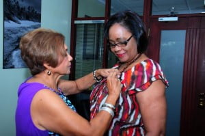 Dr. Shirley Jhagroo, Medical Coordinator of the Breast Screening Unit attaches a commemorative pin to Gracie Elias, Walk Manager for CIBC FirstCaribbean Barbados