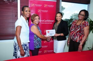 Denise Carter-Taylor (left) of the Ministry of Health and a member of the Breast Screening Board and Gracie Elias (right), Walk Manager for CIBC FirstCaribbean Barbados witness the presentation from Donna Wellington, Managing Director and Country Head for CIBC FirstCaribbean Barbados to Dr. Shirley Jhagroo, Medical Coordinator of the Breast Screening Unit.