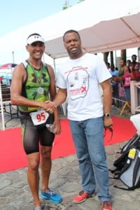Deputy Premier of Nevis and Minister of Sports Mark Brantley greets decorated Triathelete Chris McCormack, winner of the first ever MaccaX Nevis International Triathlon held on Nevis on November 16, 2013