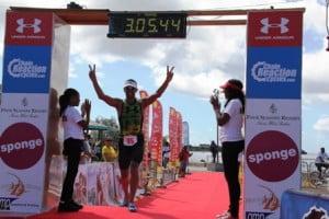 Triathelete Chris McCormack crosses the finish line during the first MaccaX Nevis International Triathlon held on Nevis on November 16, 2013
