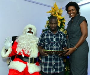 At right, Office Administrator at SOL (BARBADOS) LTD Carolyn Springer-Bryan assisting Santa Claus as he offers Shaquille Brathwaite a Christmas present at the Challenor Creative Arts & Training Centre Christmas party