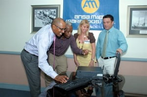 (From left) Rolf Phillips, General Manager of Consolidated Finance Company; gives Alvin Boyce, Head of Education at HMP Dodds a computer demonstration while Janet Lewis, Librarian and Nicholas Mouttet, CEO of ANSA McAL (Barbados) Limited look on.
