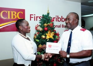 Michelle Whitelaw, CIBC FirstCaribbean's Director of Retail Banking, Barbados presents the Salvation Army's Divisional Secretary, Captain Robert Pyle with a financial contribution towards the army's programmes throughout the year at the bank's Rendezvous offices.